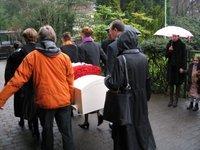 crematie, familieleden dragen de kist