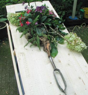Een begrafenis met gekleurd zand. een grondboor verwerkt in een bloemstuk