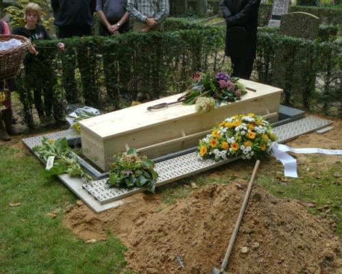 Een begrafenis met gekleurd zand. de kist op het graf